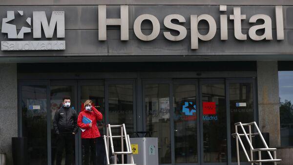 Mọi người đeo khẩu trang đứng gần bệnh viện ở Madrid - Sputnik Việt Nam