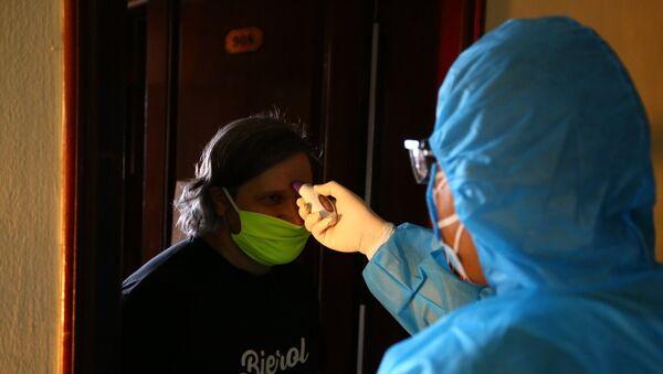 Nhân viên y tế kiểm tra thân nhiệt cho du khách nước ngoài tại khu cách ly tự nguyện ở khách sạn Bưu Điện, phường Bãi Cháy (TP Hạ Long). - Sputnik Việt Nam