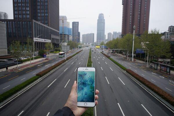 Đồng hồ điện thoại di động chỉ 12 giờ trưa trên nền đường phố vắng vẻ ở Vũ Hán trong đại dịch coronavirus - Sputnik Việt Nam