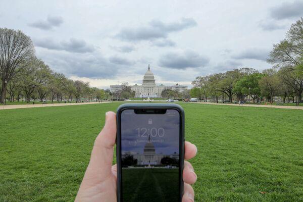 Đồng hồ chỉ 12 giờ trên điện thoại di động đối diện Tòa nhà Quốc hội Washington trong đại dịch coronavirus - Sputnik Việt Nam
