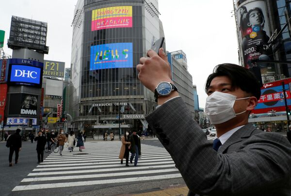 Một người đàn ông đeo khẩu trang chụp ảnh trên điện thoại di động vào buổi trưa tại ngã tư Shibuya ở Tokyo trong đại dịch coronavirus - Sputnik Việt Nam