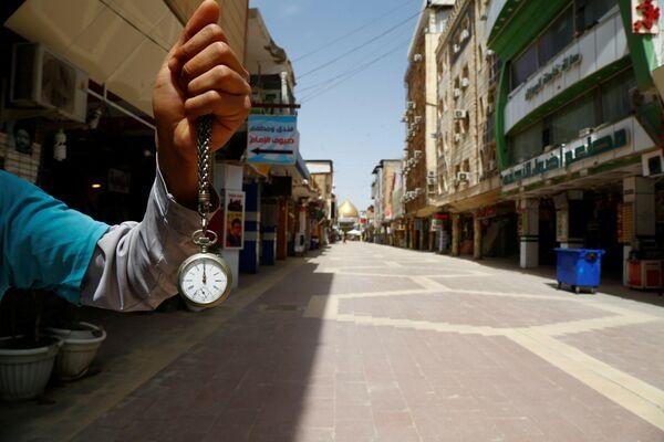 Chiếc đồng hồ bỏ túi chỉ 12 giờ trưa trên tay người đàn ông ở khu vực chợ gần nhà thờ Hồi giáo Imam Ali ở Najaf, Iraq, trong đại dịch coronavirus - Sputnik Việt Nam