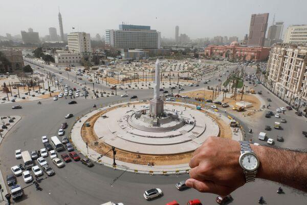 Đồng hồ đeo tay chỉ 12 giờ trưa trên nền Quảng trường Tahrir vắng người ở Cairo trong đại dịch coronavirus - Sputnik Việt Nam
