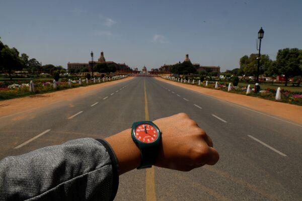 Đồng hồ đeo tay chỉ 12 giờ trưa trên nền Đại lộ Rajpath vắng người ở New Delhi trong đại dịch coronavirus - Sputnik Việt Nam
