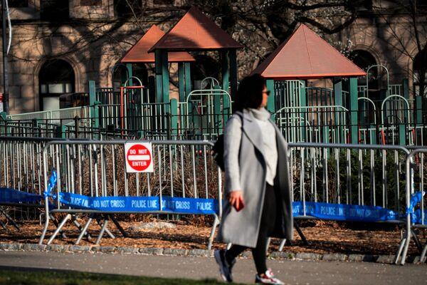 Người phụ nữ đi qua hàng rào bên sân chơi ở Công viên Trung tâm New York  - Sputnik Việt Nam
