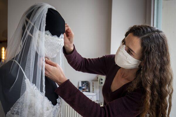 Nhà thiết kế hoàn thiện chiếc váy cưới với khẩu trang trong cửa hàng ở Berlin - Sputnik Việt Nam