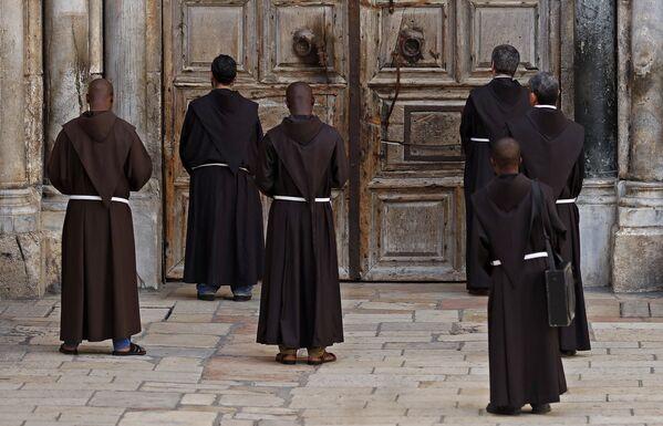 Các tu sĩ dòng Phanxicô trong buổi cầu nguyện trước cánh cửa nhà thờ đóng kín  - Sputnik Việt Nam