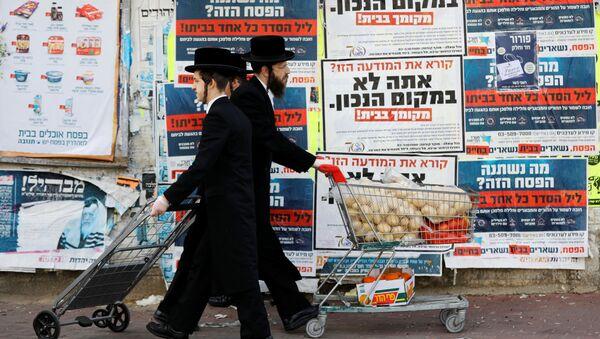Ультраортодоксальные евреи проходят мимо информационных щитов, призывающих оставаться дома из-за коронавируса в Ашдоде, Израиль - Sputnik Việt Nam