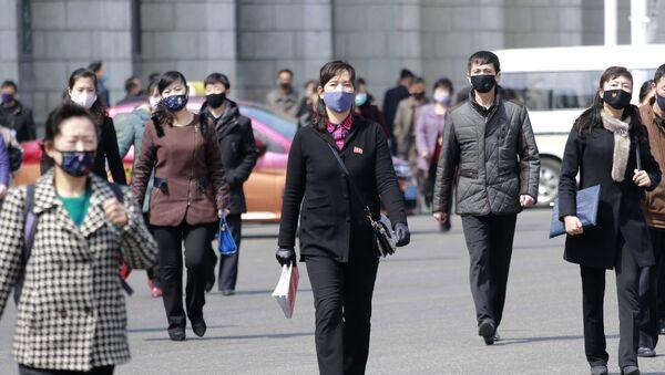Người qua đường đeo mặt nạ y tế trên đường phố ở Bình Nhưỡng, Triều Tiên - Sputnik Việt Nam
