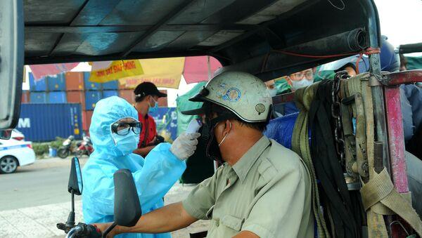 Lực lượng y tế kiểm tra thân nhiệt cho tài xế ra vào thành phố tại chân cầu Đồng Nai trên Xa lộ Hà Nội.  - Sputnik Việt Nam