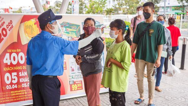 Nhân viên bảo vệ đo nhiệt độ khách hàng tại lối vào một siêu thị ở thành phố nghỉ mát Nha Trang, Việt Nam - Sputnik Việt Nam