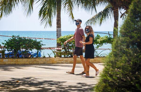 Khách du lịch đeo khẩu trang đi ngang qua một bãi biển đóng cửa giữa lúc dịch coronavirus bùng phát tại thành phố nghỉ mát Nha Trang, Việt Nam - Sputnik Việt Nam