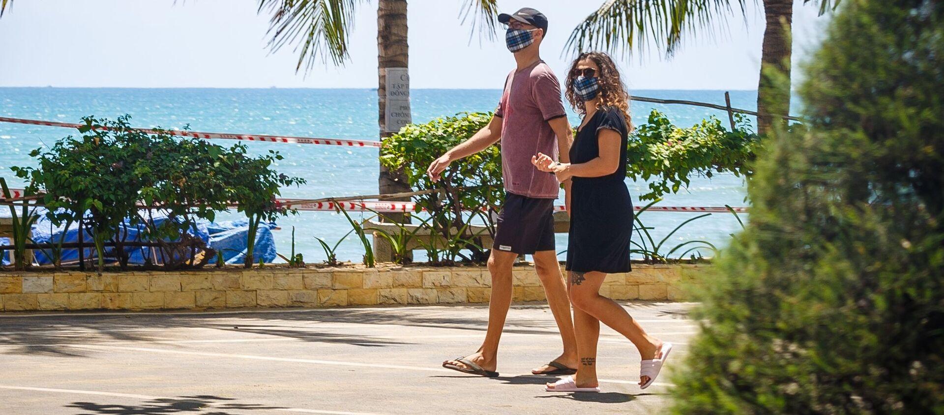 Khách du lịch đeo khẩu trang đi ngang qua một bãi biển đóng cửa giữa lúc dịch coronavirus bùng phát tại thành phố nghỉ mát Nha Trang, Việt Nam - Sputnik Việt Nam, 1920, 06.07.2021
