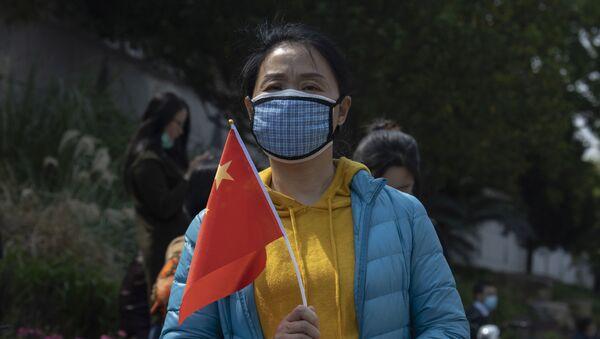Cô gái trong mặt nạ y tế với một lá cờ quốc gia. - Sputnik Việt Nam