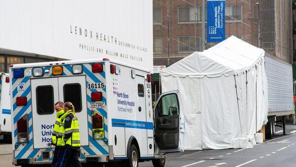 Nhân viên y tế đi ngang qua nhà xác mô phỏng bố trí phía sau Gian trưng bày Y tế Lenox Health ở New York - Sputnik Việt Nam