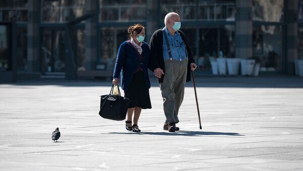 Một cặp vợ chồng người cao tuổi đeo khẩu trang trên đường phố Belgrade. - Sputnik Việt Nam