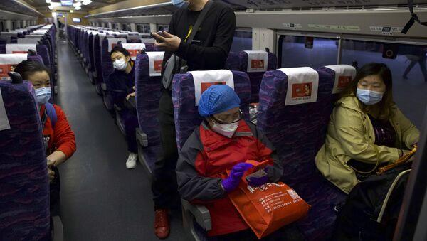 Hành khách đeo khẩu trang bảo vệ trong chuyến tàu đầu tiên sau khi nối lại giao thông ở Vũ Hán, Trung Quốc. - Sputnik Việt Nam