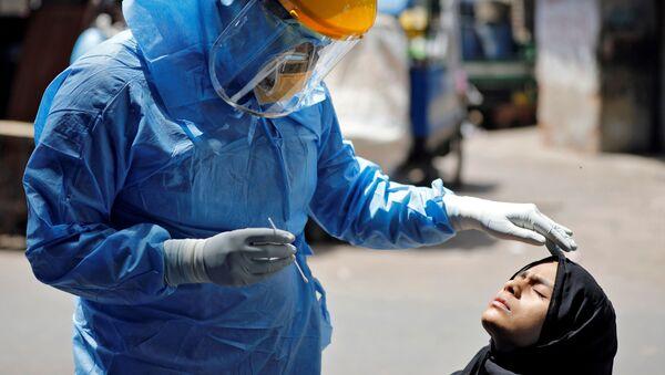 Bác sĩ mặc bộ đồ bảo vệ đang kiểm tra một cô gái bị nhiễm coronavirus ở Ahmedabad, Ấn Độ - Sputnik Việt Nam