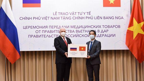 Thứ trưởng Ngoại giao Tô Anh Dũng trao vật tư y tế cho Đại sứ Liên bang Nga tại Việt Nam Konstantin Vnukov. - Sputnik Việt Nam