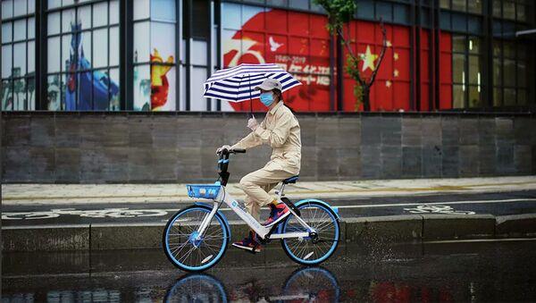 Một người phụ nữ đi xe đạp ở Vũ Hán, tỉnh Hồ Bắc. Ngày 10 tháng 4 năm 2020 - Sputnik Việt Nam