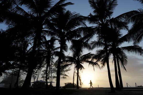 Người đàn ông đi dạo trong hoàng hôn trên bãi biển ở Rio de Janeiro, Brazil - Sputnik Việt Nam