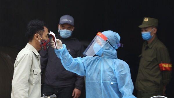 Nhân viên y tế kiểm tra thân nhiệt của người dân thôn Đông Cứu. - Sputnik Việt Nam