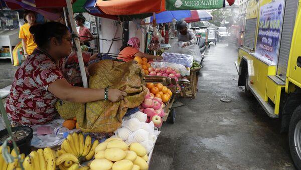 Nhân viên bán hàng đóng cửa trái cây từ việc phun thuốc tại một khu chợ ở Manila - Sputnik Việt Nam
