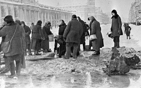 Cư dân thành phố Leningrad bị bao vây lấy nước từ một lỗ trên đường nhựa xuất hiện sau vụ pháo kích - Sputnik Việt Nam