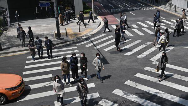 Những người đeo khẩu trang đang băng qua ngã tư dành cho người đi bộ ở Seoul, Hàn Quốc - Sputnik Việt Nam
