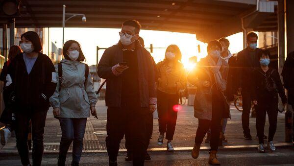 Người qua đường đeo mặt nạ bảo vệ trên một trong những con phố của Bắc Kinh, Trung Quốc - Sputnik Việt Nam