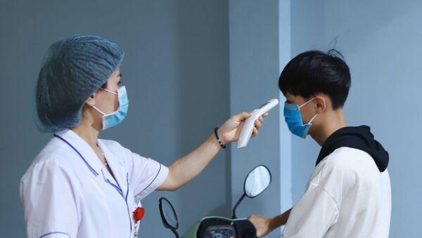 Lực lượng y tế đo thân nhiệt người dân khi vào bệnh viện. - Sputnik Việt Nam