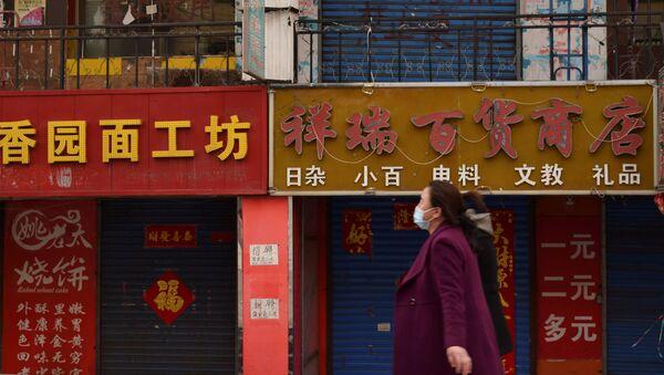 Người phụ nữ đeo mặt nạ đi qua các cửa hàng đóng cửa - Sputnik Việt Nam