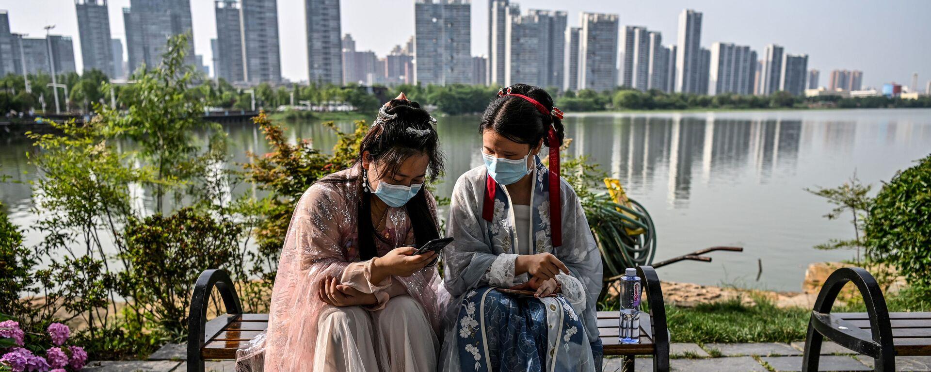 Phụ nữ trẻ đeo khẩu trang và bận trang phục truyền thống trên băng ghế ở công viên Vũ Hán, Trung Quốc - Sputnik Việt Nam, 1920, 08.06.2020