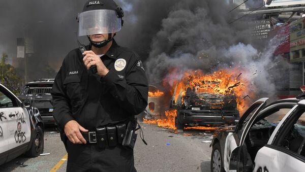Cảnh sát Los Angeles trên nền chiếc xe bị đốt cháy trong cuộc biểu tình - Sputnik Việt Nam