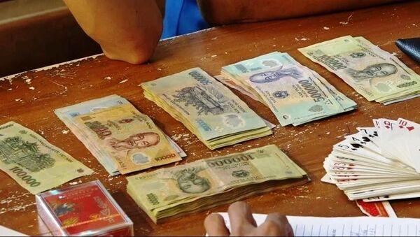 Tang vật thu giữ tại sới bạc của đối tượng Lê Thị Thuận gồm số tiền gần 40 triệu đồng, 03 điện thoại di động, 03 bộ bài tú lơ khơ. - Sputnik Việt Nam