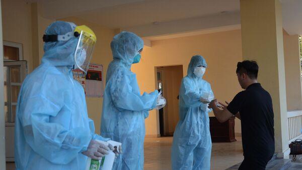 Nhân viên y tế khử trùng tay, phát khẩu trang y tế cho công dân trở về từ Hàn Quốc. - Sputnik Việt Nam