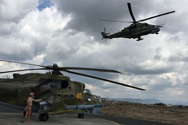 """Một nhân viên kỹ thuật bên cạnh trực thăng tấn công Mi-24 của Nga ở sân bay """"Hmeymim"""", Syria - Sputnik Việt Nam"""