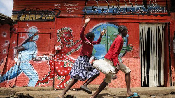 Trẻ em chạy trước tranh tường graffiti về coronavirus trong khu ổ chuột Kibera ở Nairobi, Kenya - Sputnik Việt Nam
