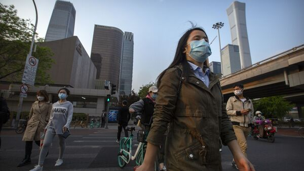 Người qua đường đeo khẩu trang trên nền các tòa nhà chọc trời ở khu thương mại Bắc Kinh, Trung Quốc. - Sputnik Việt Nam
