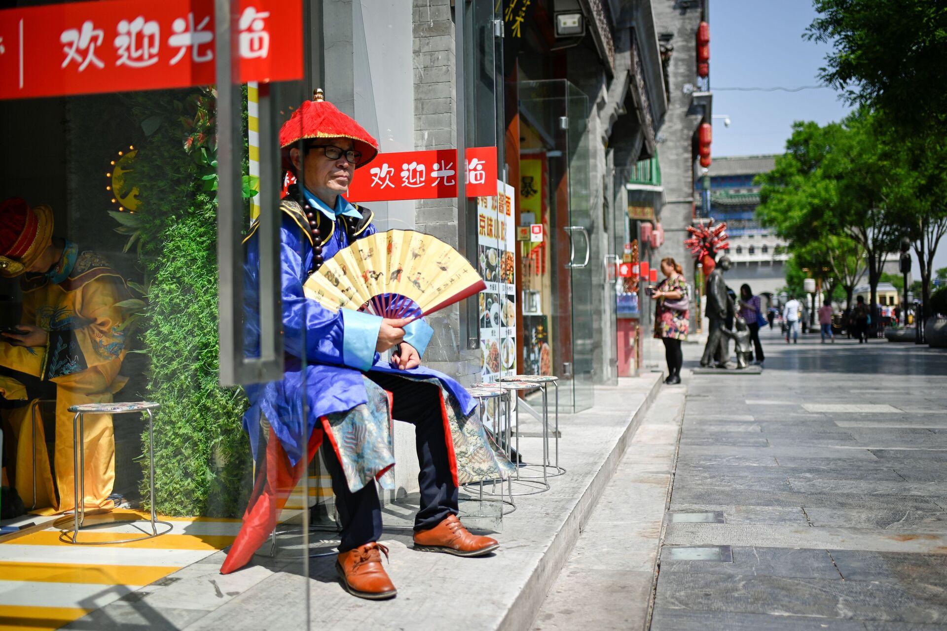 Người bán hàng bên lối vào một cửa hàng trên một con phố ở Bắc Kinh, Trung Quốc - Sputnik Việt Nam, 1920, 05.10.2021