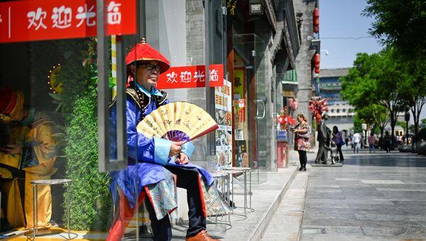 Người bán hàng bên lối vào một cửa hàng trên một con phố ở Bắc Kinh, Trung Quốc - Sputnik Việt Nam