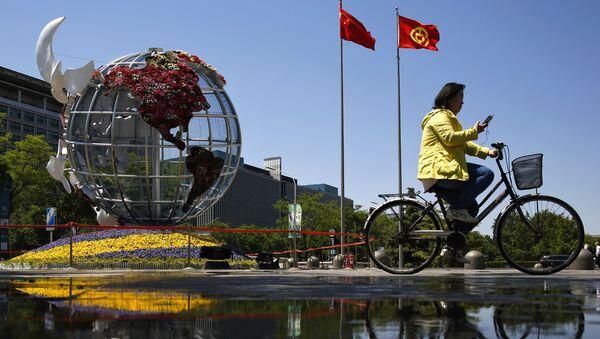 Một người phụ nữ đi xe đạp ở quảng trường trước một ngân hàng ở Bắc Kinh. - Sputnik Việt Nam