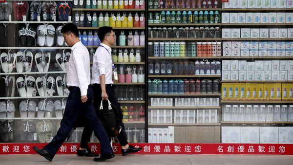 Đàn ông đi ngang qua cửa sổ cửa hàng ở Bắc Kinh, Trung Quốc. - Sputnik Việt Nam