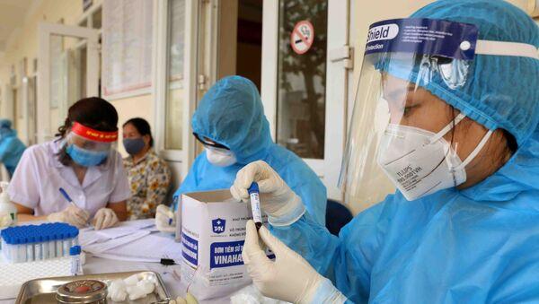 Nhân viên y tế của Trung tâm kiểm soát bệnh tật thành phố (CDC Hà Nội) tiến hành lấy mẫu xét nghiệm COVID-19. - Sputnik Việt Nam