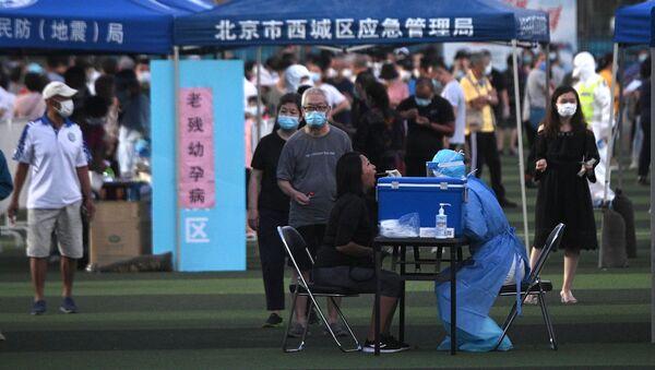 Một nhân viên y tế kiểm tra một cô gái bị nhiễm coronavirus ở Bắc Kinh - Sputnik Việt Nam