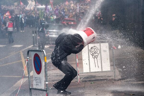 Người biểu tình đội chiếc xô tránh súng nước của cảnh sát tại cuộc biểu tình phản đối của các nhân viên ngành y ở Nantes, Pháp - Sputnik Việt Nam