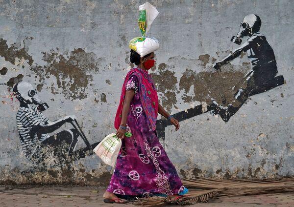 Người phụ nữ đeo khẩu trang đi ngang qua tranh graffiti ở Mumbai, Ấn Độ - Sputnik Việt Nam