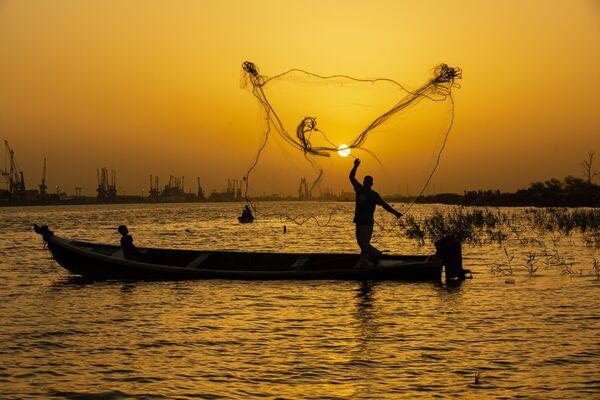 Ngư dân tung lưới lúc hoàng hôn trên sông Shatt al-Arab ở thành phố Basra, Iraq - Sputnik Việt Nam