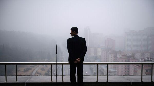 Một người đàn ông trên ban công một ngôi nhà ở Bình Nhưỡng vào một ngày sương mù - Sputnik Việt Nam