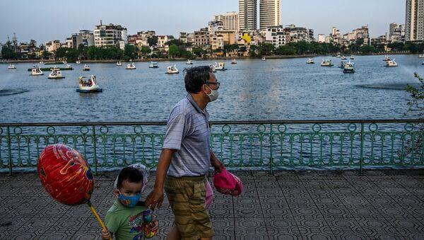 Một người đàn ông và một đứa trẻ đeo mặt nạ đi dạo bên hồ ở Hà Nội, Việt Nam - Sputnik Việt Nam
